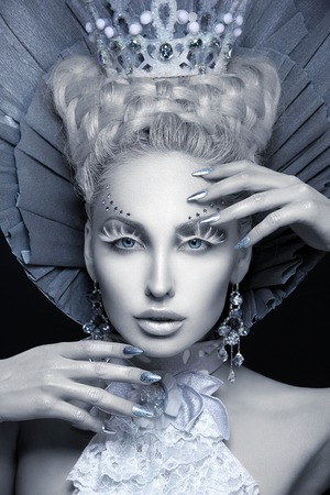 Closeup portrait of beautiful young woman dressed as winter queen. Creative makeup. Over black background. Copy space. Stock Photo