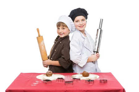 christmas baker's: Beautiful boy and girl in chef clothes making christmas cookies with plunger over white background. Isolated. Copy space.