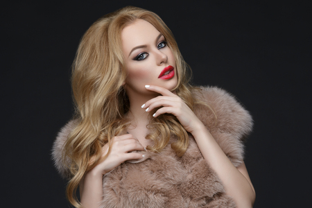 Beautiful young woman with bright makeup, red lips and long blond hair standing in fur coat. Studio shot over dark background. Copy space. Stock Photo