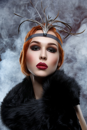 full red: Beautiful young woman with smoky eyes and full red lips in fur. Vintage head piece. Studio beauty shot over smoky background. Copy space.