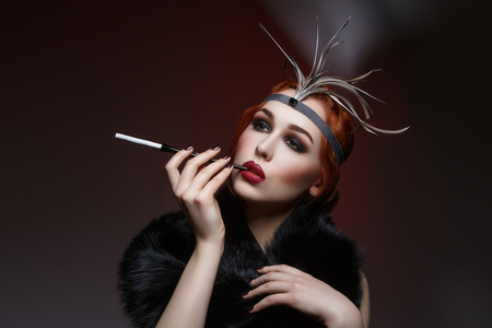 full red: Beautiful young woman with smoky eyes and full red lips holding cigarette holder. Vintage head piece. Retro styling. Studio beauty shot. Copy space.