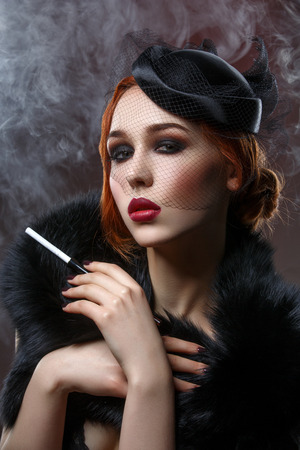 full red: Beautiful young woman with smoky eyes and full red lips holding cigarette holder. Vintage head piece. Retro styling. Studio beauty shot over smoky background. Copy space.