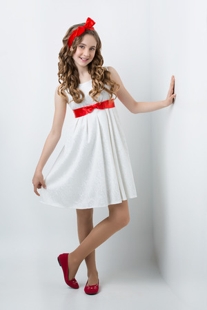 female child: Beautiful teenage girl with long curly hair and red ribbon bow on head wearing white dress standing near wall. Happy expression. Studio portrait on white background. Copy space.