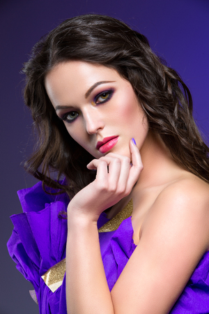 smoky eyes: Beautiful brunette young woman with dark smoky eyes make-up in paper dress. Beauty shot over dark background. Copy space.
