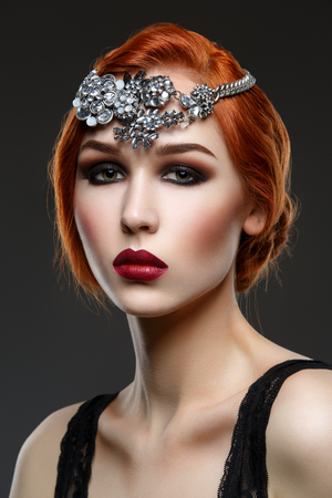 full red: Beautiful young woman with smoky eyes and full red lips. Massive crystal hair accessory on head. Studio beauty shot. Copy space. Stock Photo