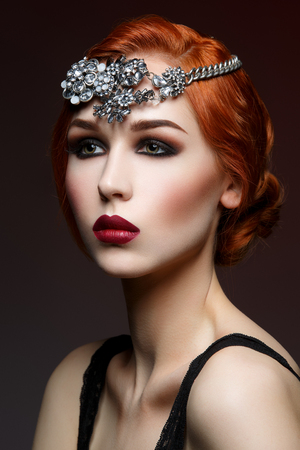 smoky eyes: Beautiful young woman with smoky eyes and full red lips. Massive crystal hair accessory on head. Studio beauty shot. Copy space. Stock Photo