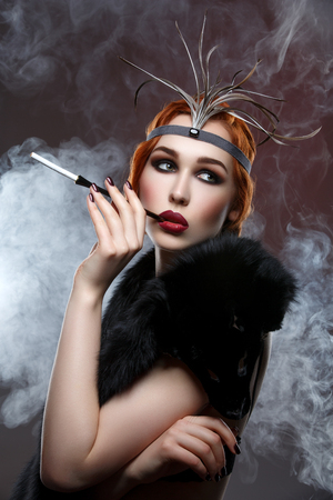 smoky eyes: Beautiful young woman with smoky eyes and full red lips holding cigarette holder. Vintage head piece. Retro styling. Studio beauty shot over smoky background. Copy space.