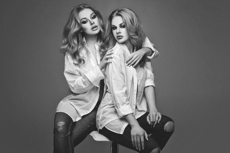 Two beautiful young women with long blond hair and makeup wearing white men shirts and jeans sitting over grey background. Sisters. Studio shot. Copy space. Monochrome. Standard-Bild