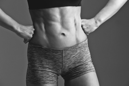 sudio: Closeup of fit woman torso with abs muscles. Body part. Fitness. Sudio shot over grey background. Monochrome. Stock Photo