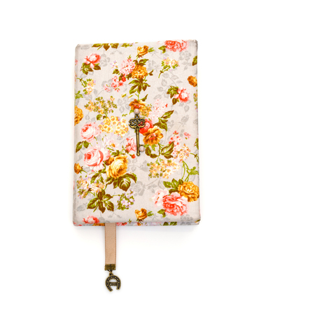 Beautiful handmade paper notebook in hard floral cover. Bokmark ribbon with horseshoe pendant detail. Scrapbooking. Isolated on white. Copy space.