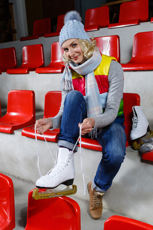 natural ice pastime: Beautiful blond young woman in winter clothes sitting on red tribune and putting on white skates. Girl getting ready for skating on ice rink. Stock Photo