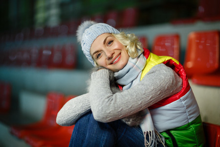 Beautiful blond young woman in winter clothes sitting on ice rink tribune. Dreaming expression. Stock Photo