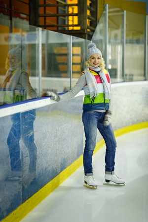 natural ice pastime: Beautiful blond young woman in winter clothes and white skates standing on ice rink.