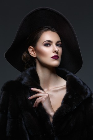 Beautiful young woman with glamorous make-up in luxurious fur coat and fashion hat on black background. Copy space.