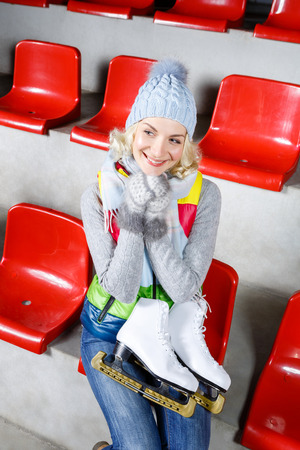 natural ice pastime: Beautiful blond young woman in winter clothes sitting on red tribune and holding white skates Stock Photo