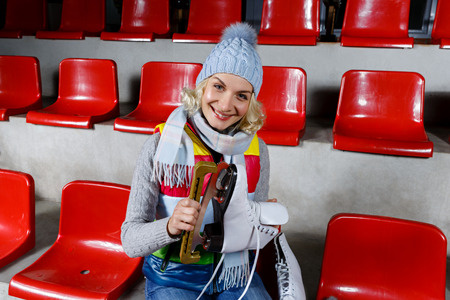 tribune: Beautiful blond young woman in winter clothes sitting on red tribune and holding white skates Stock Photo