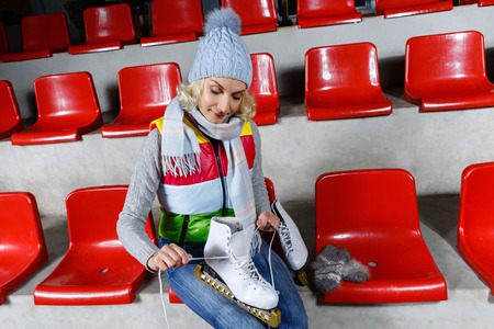 Beautiful blond young woman in winter clothes sitting on red tribune and holding white skates Stock Photo