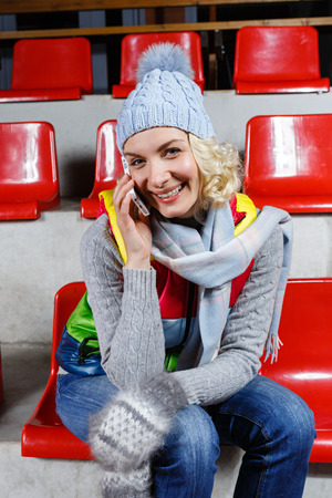 natural ice pastime: Beautiful blond young woman in winter clothes sitting on red tribune and talking on the mobile phone