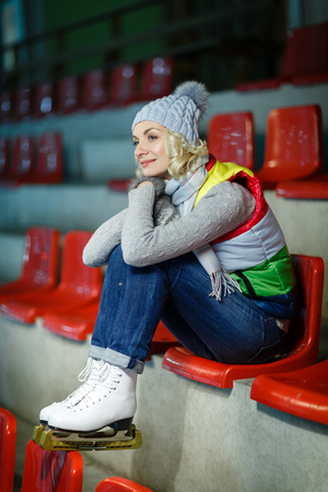 natural ice pastime: Beautiful blond young woman in winter clothes and white skates sitting on red tribune. Girl is ready for skating on ice rink. Stock Photo
