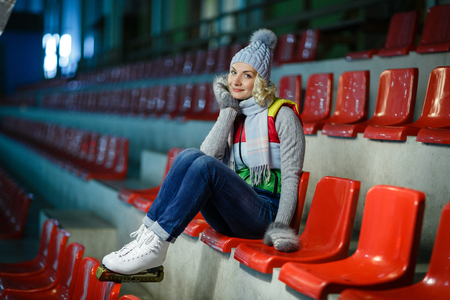 Beautiful blond young woman in winter clothes and white skates sitting on red tribune. Girl is ready for skating on ice rink. Stock Photo
