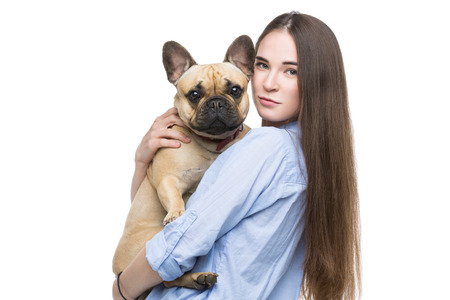 Beautiful young woman with long hair in jeans shirt holding adult french bulldog girl. Studio shot isolated on white. Copy space.