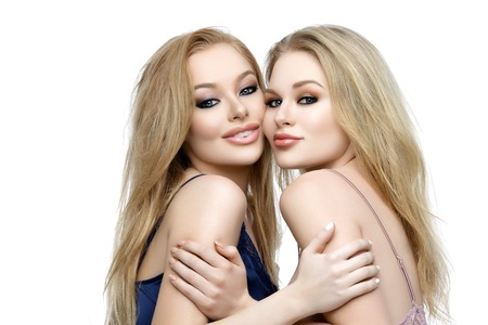 Two happy beautiful blond young women with makeup in night wear. Isolated over white background. Copy space.
