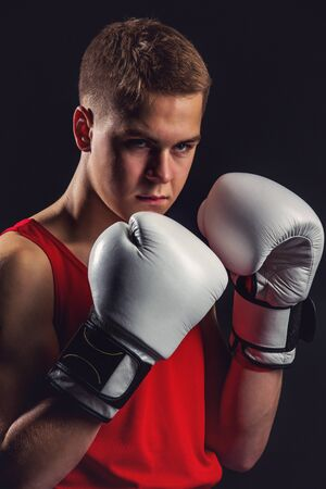 Young handsome boxer sportsman in red boxer suit and white gloves standing on black backgound. Copy space. Stock Photo