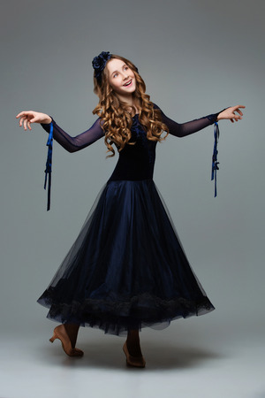 curtsy: Beautiful teenager ballroom dancer with long blond hair in long dark blue dress making curtsy. Studio shot on grey background. Copy space. Stock Photo