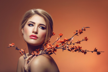 Beautiful girl with sakura branch Stock Photo