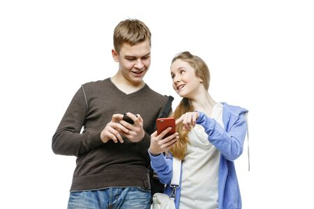 habbit: Teen boy and girl standing with mobile phones