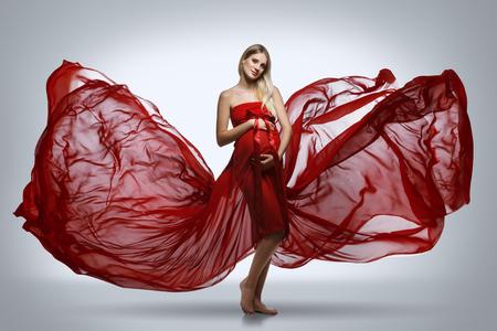 Chica embarazada en vestido rojo Foto de archivo