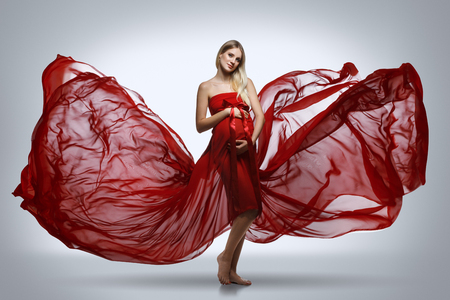 Schwangere Mädchen im roten Kleid Standard-Bild