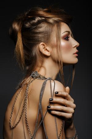sexualidad: Hermosa chica con muchas cadenas de oro y bronce