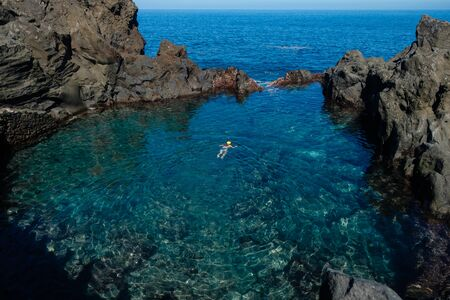 young woman swimming in natural ocean swimming pool on Tenerife island. outdoor shot in Spain. copy space.