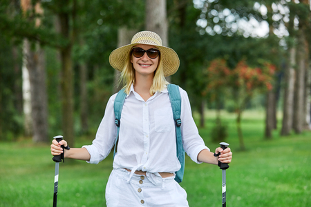 young woman with nordic walk pols