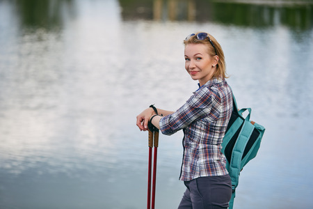 young woman with nordic walk pols 스톡 콘텐츠