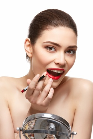 girl applying red lipstick isolated on white
