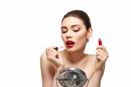 girl applying red lipstick isolated on white