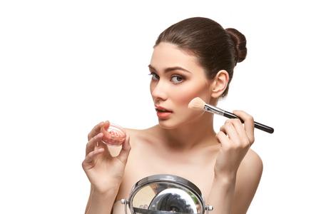 girl applying blush on face isolated on white
