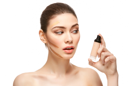 girl applying foundation on face isolated on white Stock Photo