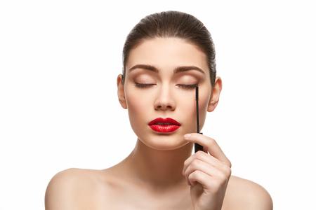 girl applying eyelash mascara isolated on white