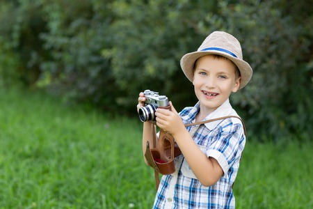 handsome little boy with retro camera outdoors Stock Photo