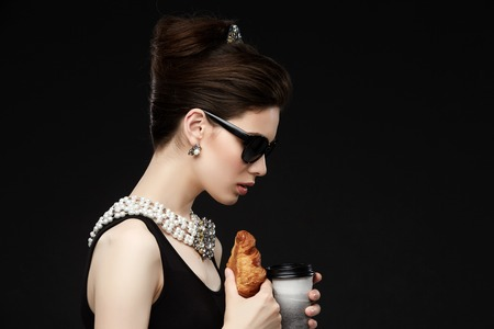 beautiful young woman in retro style with croissant Stock Photo