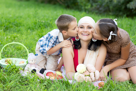 mother with two kids having picnic outdoors