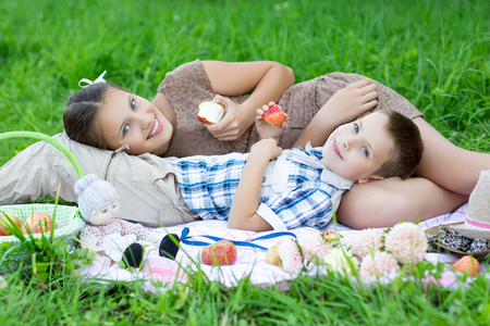 Little boy and teen age girl having picnic outdoors Stock fotó