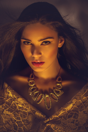 beautiful young woman with necklace in golden light