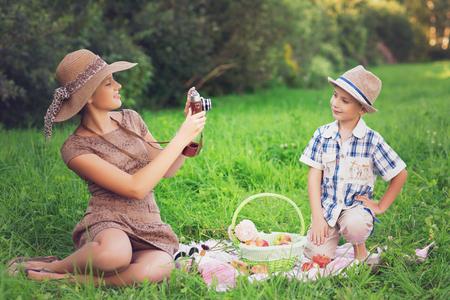 Little boy and teen girl having picnic outdoors