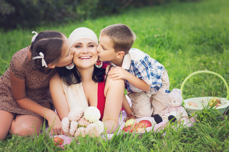 mother with kids having picnic outdoors Stock Photo