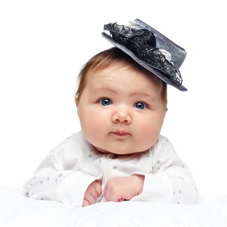 beautiful baby girl in fancy hat on white blanket