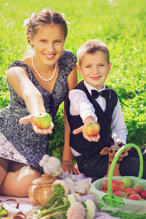 Little boy and teen age girl having picnic outdoors Stock Photo